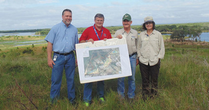 """Ross Dickerson, manager of Hillsborough County's Environmental Lands Acquisition and Protection Program (ELAPP), Hillsborough County Commissioner Stacey White, Brandt Henningsen and Nancy Norton of SWIM stand atop """"Mount Rock Ponds."""" Photo by Vicki Parsons."""