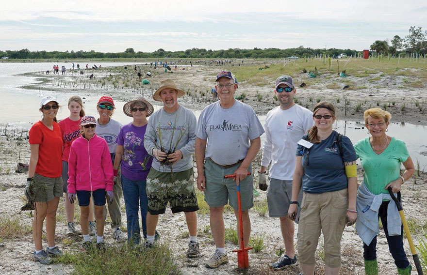 Volunteers take a break from planting marsh grasses. Photo by Vicki Parsons.